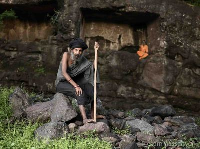 Jogi Balaknath Baba sits for a portrait in front of the cave he lives cut into the rock in Nashik, India.